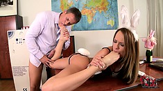 Sitting on the desk, a sexy blonde with a perfect ass displays her footjob skills