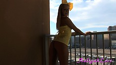 Blonde dressed in yellow with a bow poses on the balcony for pictures