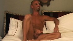 Gay stud Kirk Nadir sits on the bed jerking his meat, till he gets sucked