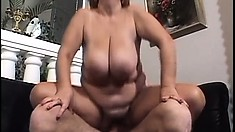 Nasty redhead cougar with massive boobs has a young guy satisfying her sexual needs