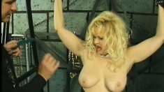 Busty blonde slave is bound and punished by her dominant master