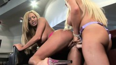 Two big breasted blonde lesbians having fun with a strap-on dildo