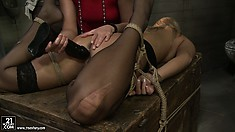 Kathia drills the blonde's twat with a black dildo and moans of pleasure fill the room