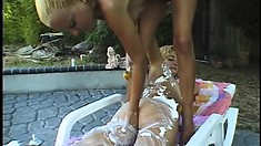 Sexy lesbians get horny and start rubbing each other poolside